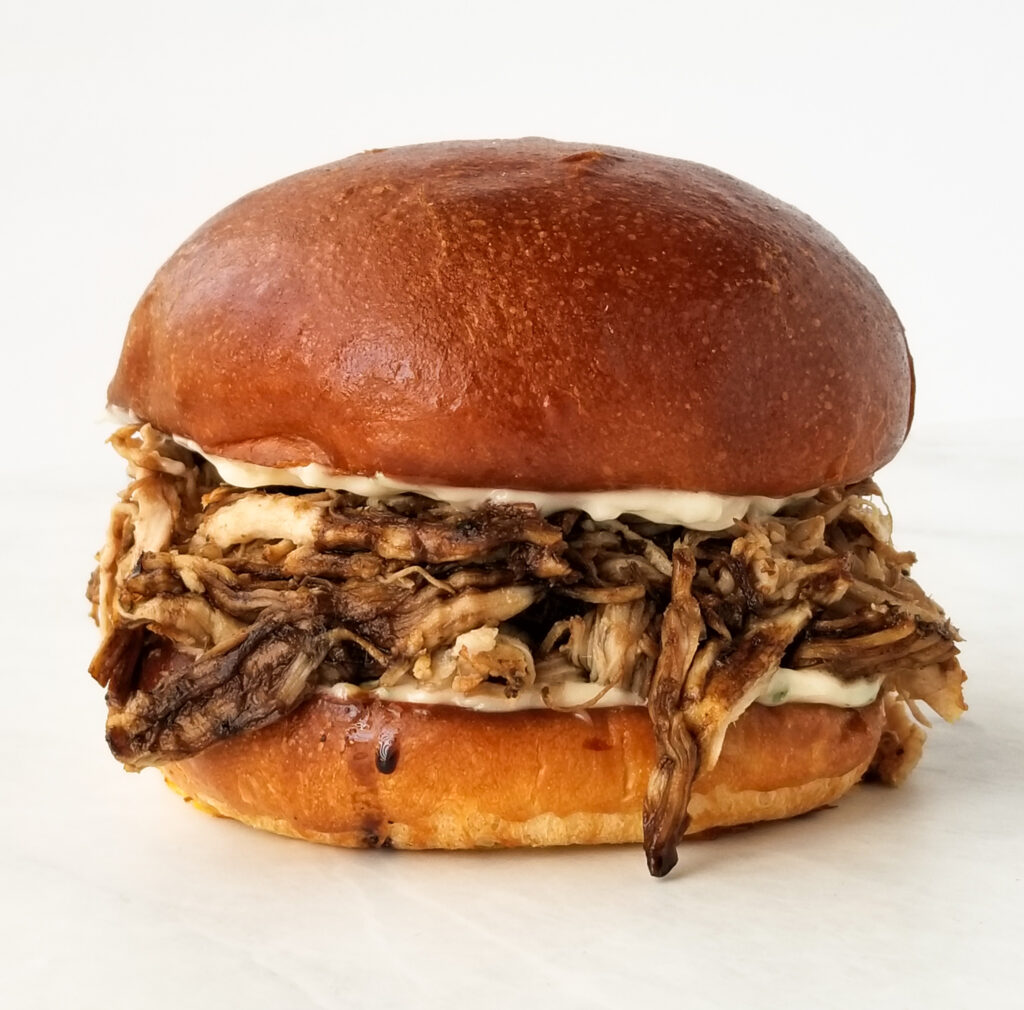 sandwich with pulled pork and mayo on white background