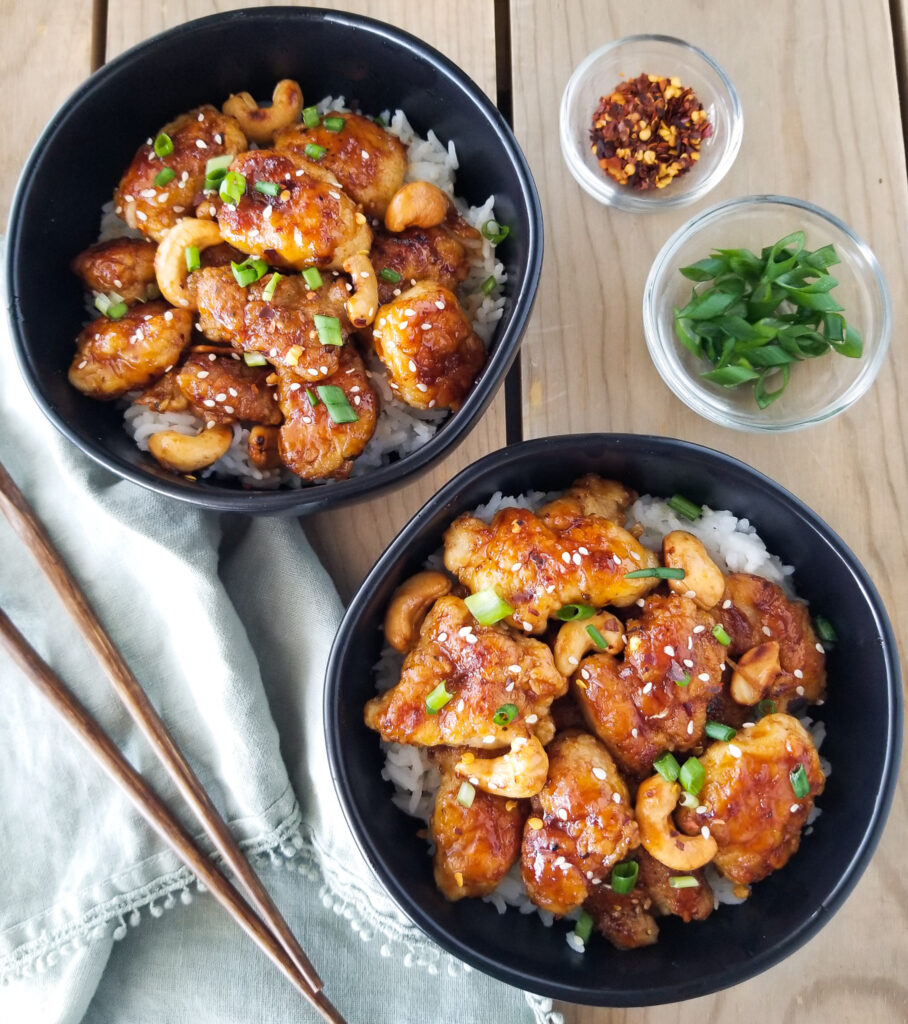two black bowls with spicy cashew chicken and rice