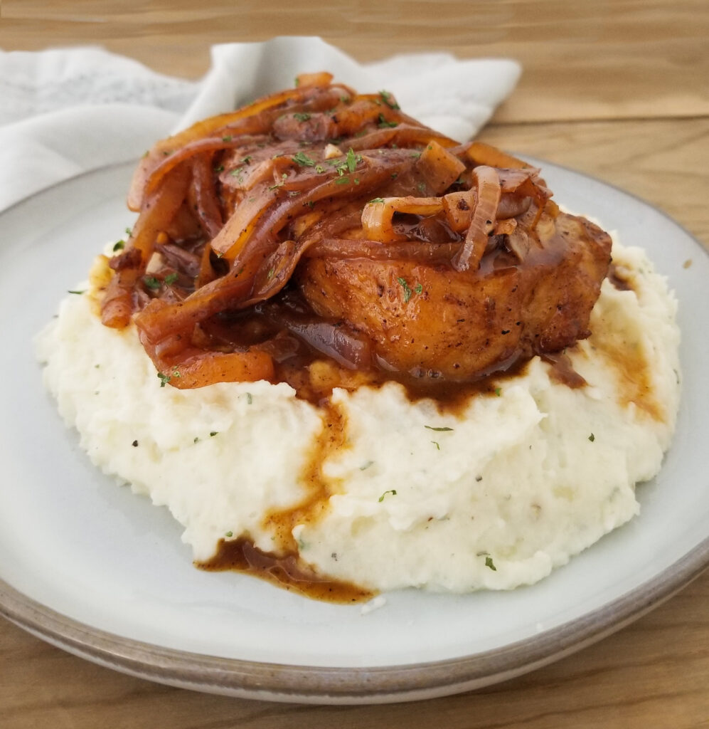 french onion pork chop on gray plate